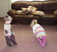 Kids picture of two toddlers playing holding a leash on one playing dog.JPG