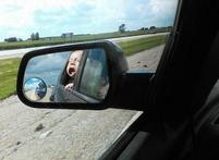 Funny baby photos of a baby opens mouth catching the air viewing from the side mirror.JPG