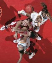 Women basketball players make funny expressions as they go for the jump ball.jpg