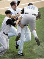 A baseball player tackles another.jpg
