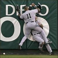 Funny pic of a baseball player smashing into another outfielder against the wall.jpg