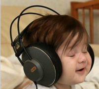 Funny toddler picture listens to music with a big head phone.PNG