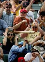 A group of baseball fans are freaked out by an incoming flying bat.jpg