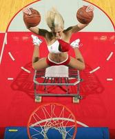 Funny photo of an NBA cheerleader trying to dunk to basketballs of a trampoline.jpg