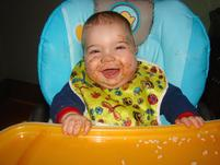 A baby with pasta sauce on face laughing.jpg