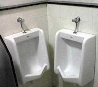 Funny picture of two urinals next to each other in the corner.JPG