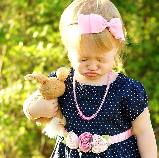 Funny pic of a little girl pouting while holding a toy bunny.jpg