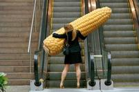 funny photo of a woman holding a gian corn.jpg