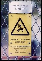 Ironic funny sign of a Danger of Death sign on cemetary fence.jpg