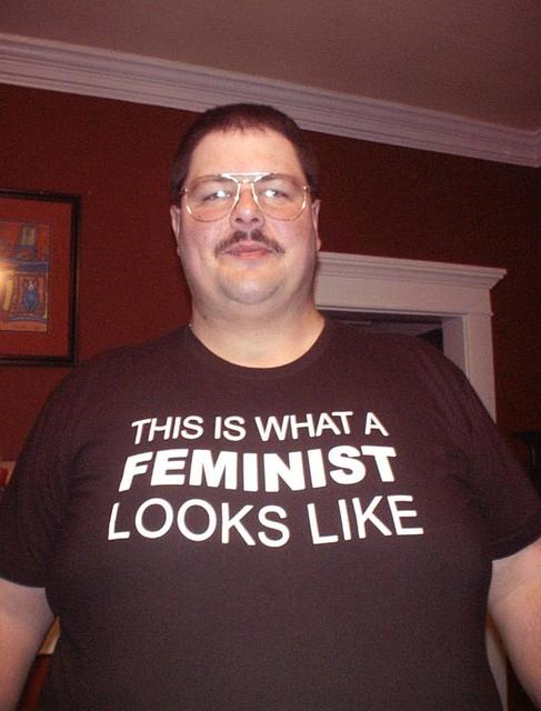 Fat man wearing a shirt that says This is What Feminist Looks Like.jpg
